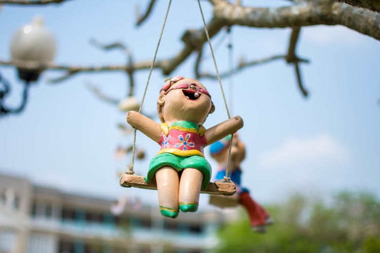 Low angle view doll hanging on swing against sky