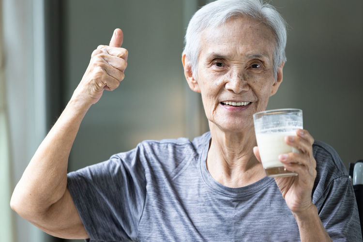 Portrait of senior woman gesturing while drinking milk