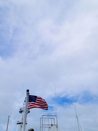 Low angle view of flag flags against sky