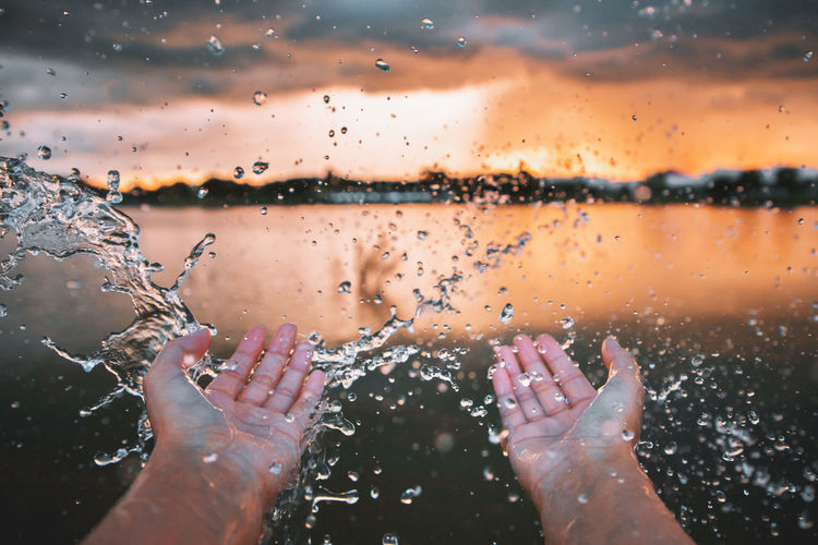 Cropped hands of person splashing water during sunset
