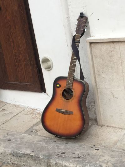 Musical Instrument Music String Instrument Guitar Musical Equipment Arts Culture And Entertainment Wall - Building Feature Musical Instrument String String No People Day Wood - Material Still Life Indoors  Built Structure Brown Architecture Wind Instrument Single Object Acoustic Guitar
