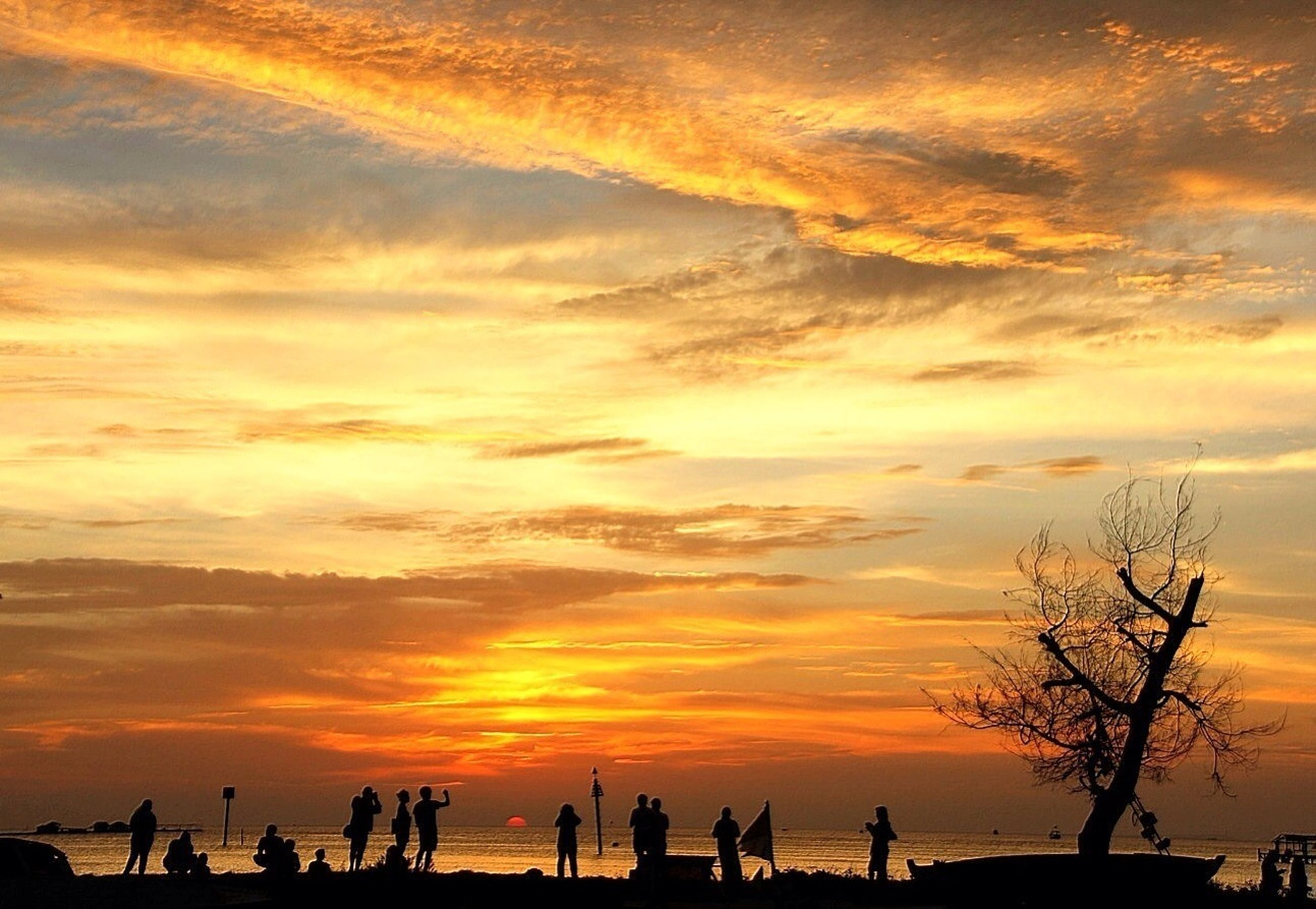 sunset, sky, orange color, silhouette, sea, scenics, beauty in nature, cloud - sky, beach, water, tranquility, tranquil scene, horizon over water, nature, idyllic, large group of people, vacations, cloud, dramatic sky