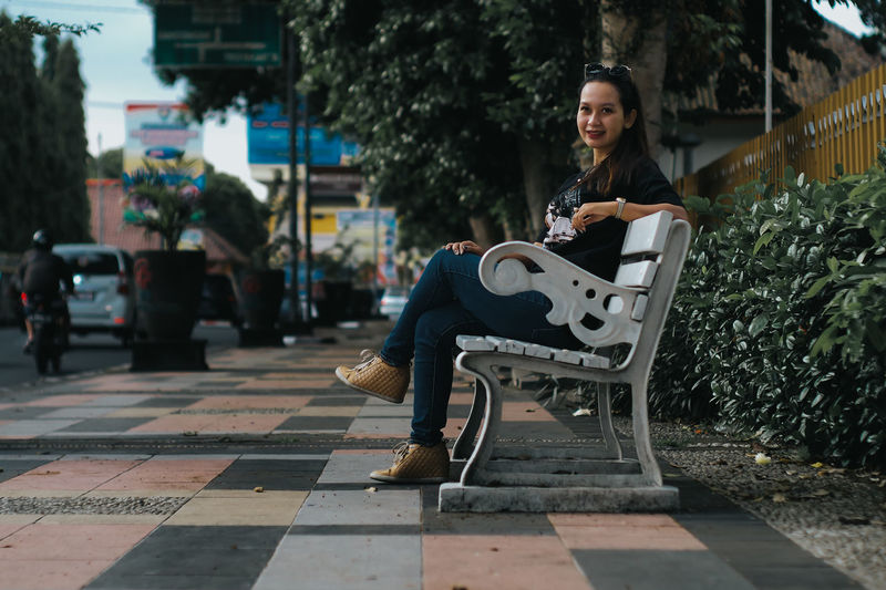 Full Length Of Woman Sitting On Bench In City