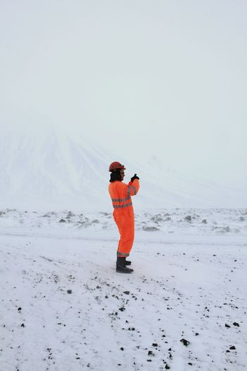 Side view of man wearing protective workwear standing on snow against clear sky