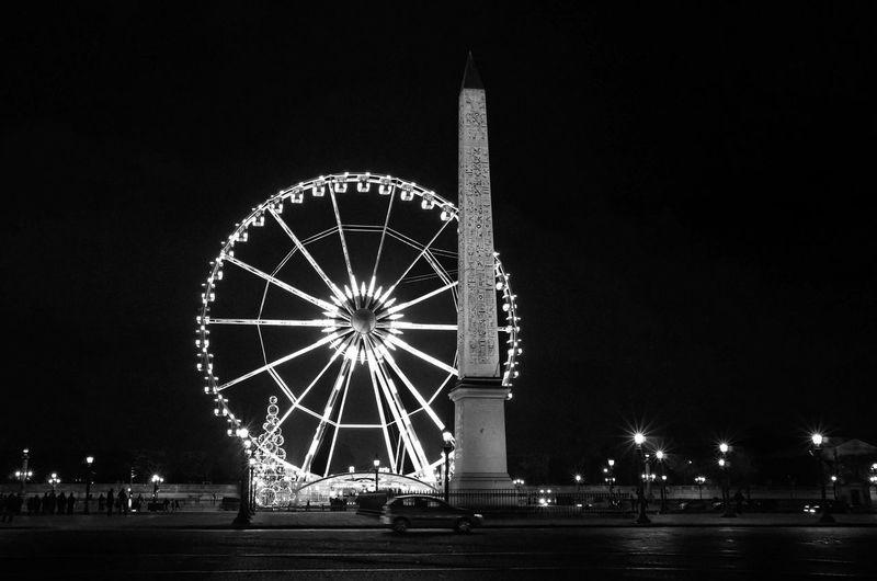 Luxor obelisk against illuminated roue de paris