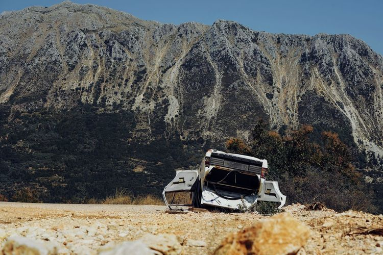 Abandoned car on field against mountain