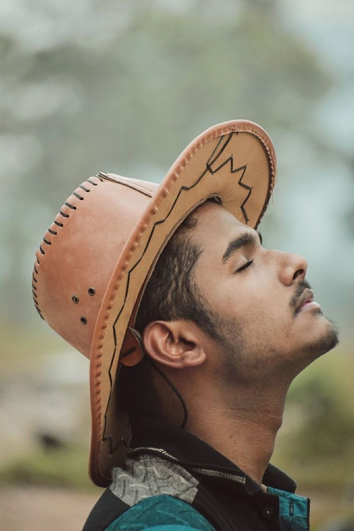 Young man with closed eyes wearing hat