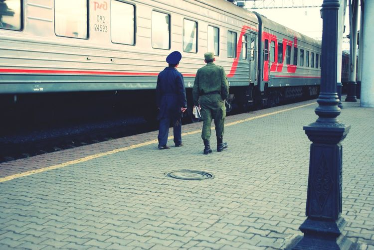 Russia 2013 : Train conductor of my carriage (or Provodnik) in blue uniform and his military friend were talking together when they met up here. This photo was taken from my Russia trip's – during a train stop running at railway station. All passenger could get off the train in 20 minutes for relaxing, buying some food, or just walking around... People Photography Destination Train Meeting Friends Russia Moment Travel People Men Train - Vehicle Railroad Station Platform Public Transportation It's About The Journey