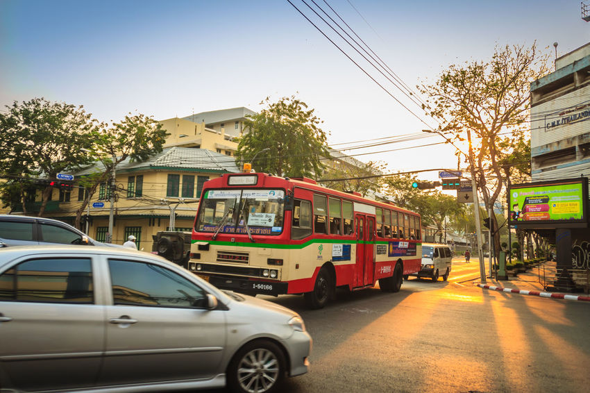 Bangkok, Thailand - March 2, 2017: Local bus and cars in traffic passes through a busy junction during sunset in Bangkok, Thailand. Sunlight Traffic Traffic Jam Traffic Signs Trafficlight Architecture Building Exterior Built Structure Cable Car City Clear Sky Day Electricity  Incidental People Junctionsquare Land Vehicle Mode Of Transportation Motor Vehicle Nature Outdoors Public Transportation Road Sky Street Sunbeam Sunrise Sunset Sunshine Traffic Arrow Sign Traffic Control Traffic Flow Traffic Light  Traffic Lights Traffic Sign Traffic Signal Trafficjam Trafficlights Transportation Tree