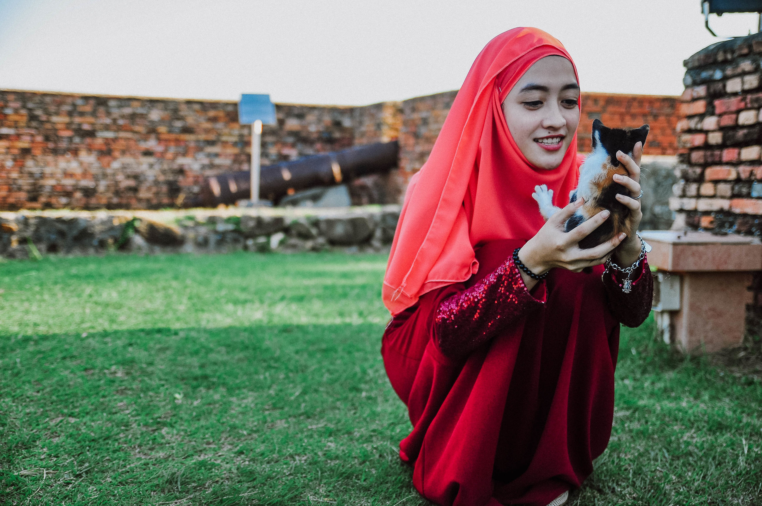 leisure activity, one person, traditional clothing, hood - clothing, grass, real people, holding, red, outdoors, hooded shirt, young adult, young women, lifestyles, day, full length, smiling, beautiful woman, sky, adult, people