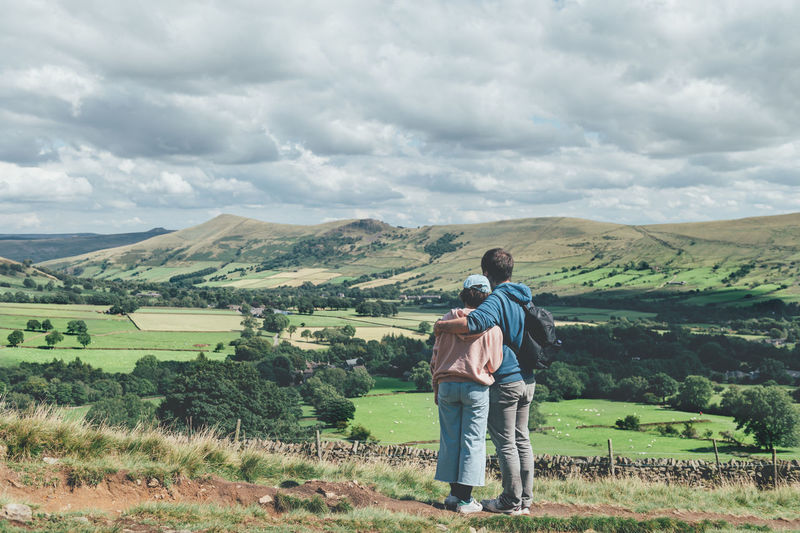 Rear view of man looking at landscape against cloudy sky