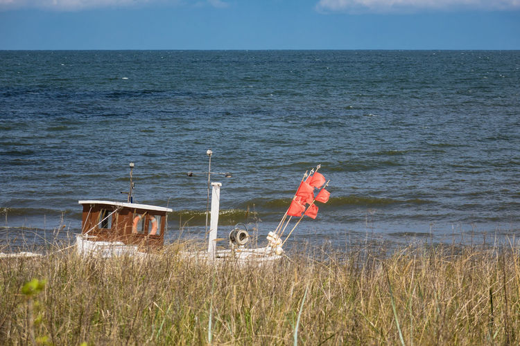 Fishing boat on the Baltic Sea coast. Baltic Sea Holiday Relaxing Beach Beauty In Nature Cloud - Sky Coast Day Dune Fishing Boat Horizon Over Water Journey Koserow Landscape Nature No People Outdoors Sea Shore Sky Tourism Travel Destinations Usedom Vacation Water