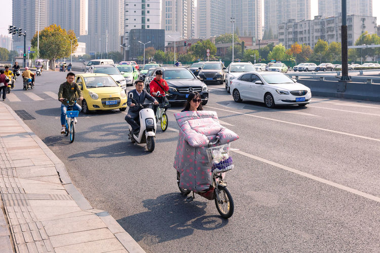 People riding motorcycle on city street