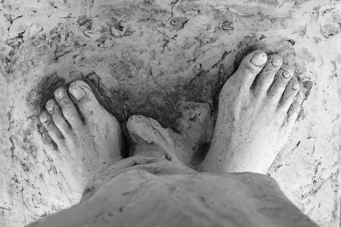 Extreme close-up of the feet of Jesus Christ. Top view. Shallow depth of field. Art Bible Calvary Catholic Christ Christian Christianity Death Detail Easter Faith Feet Foot God Holy Icon Isolated Jesus Love Nail Pain Passion Pray Prayer Red