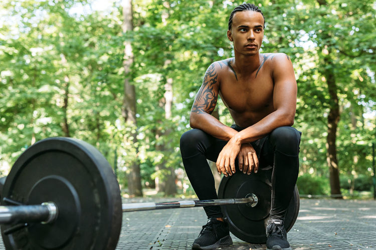 Full length of shirtless young man sitting on barbell outdoors