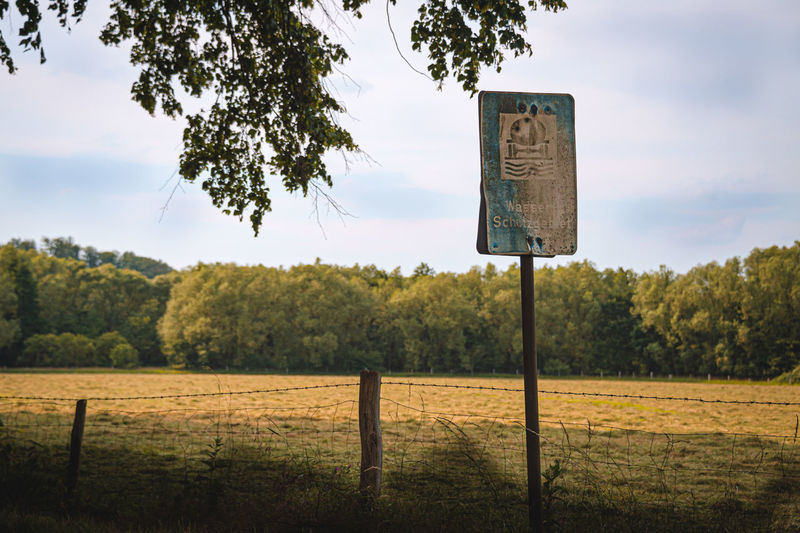 Information sign on wooden post on field against sky