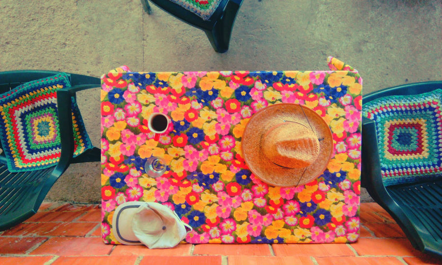 Outdoors Table Chairs Chairs And A Table Hat Multi Colored Flower Pattern Flower Patterns Straw Hat Sun Hat No People Daytime Daytime Photography Terrace Home Is Where The Art Is