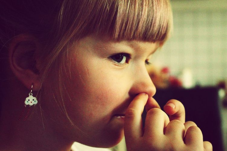 Close-up of girl with finger in nose at home
