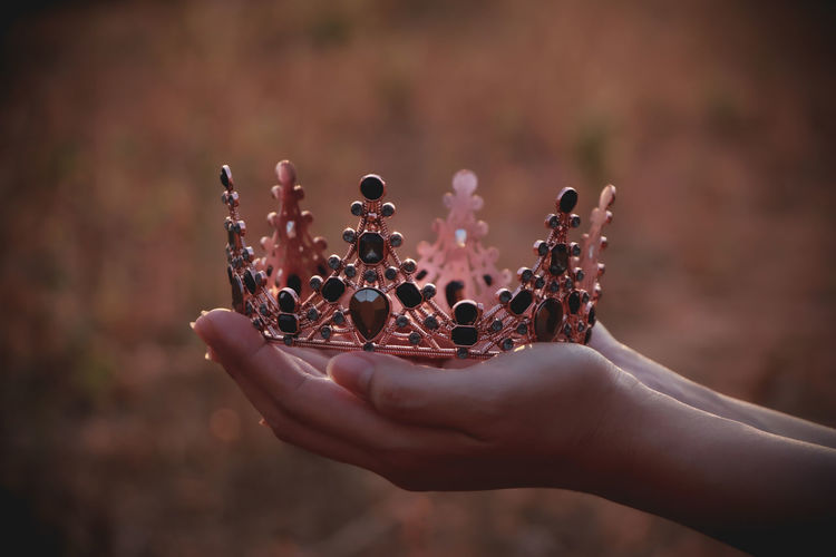 Close-up of woman holding crown.
