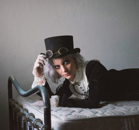Portrait of woman wearing costume while lying on bed at home