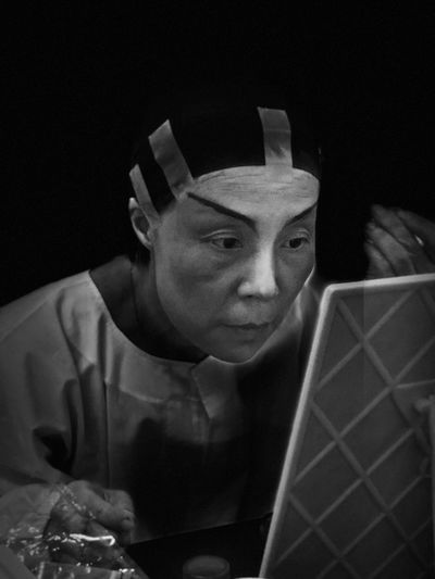 Mature Woman With Make-Up Looking Into Mirror In Darkroom