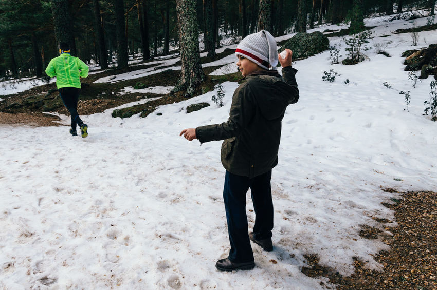 Boy paying with snowballs and runner on background Casual Clothing Cold Temperature Day Full Length Fun Leisure Activity Lifestyles Nature Person Playing Rear View Runner Season  Snow Snowballs Togetherness Tranquil Scene Walking Warm Clothing Weather Winter WoodLand