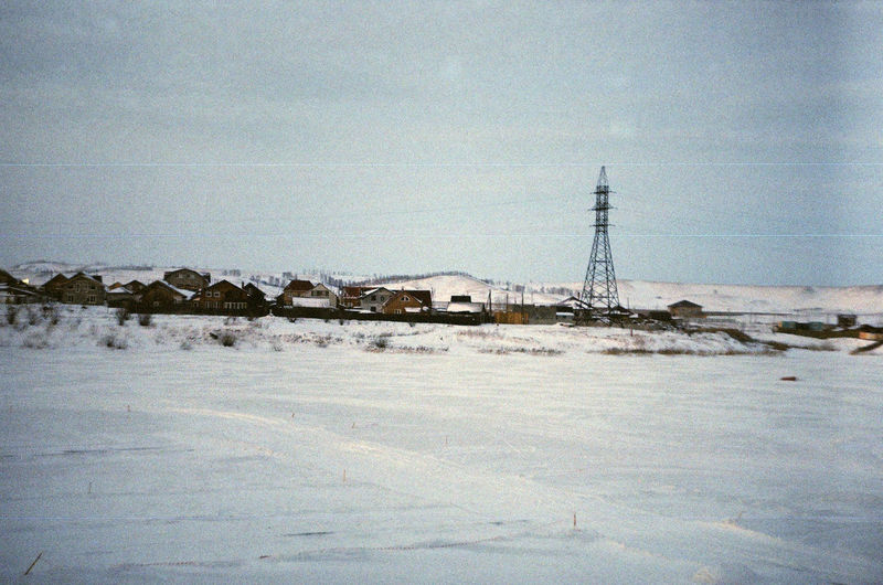 Snow covered land by building against sky