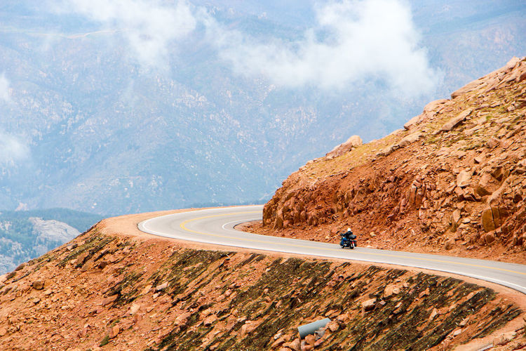 Man Riding Motorcycle On Road Against Mountain