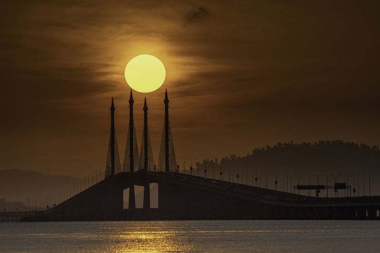 Silhouette penang bridge over sea against sky during sunset