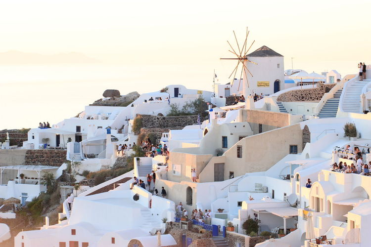 Tourists visiting village at santorini against clear sky during sunset