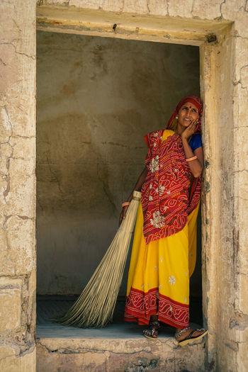 Portrait of woman with broom standing at door of house