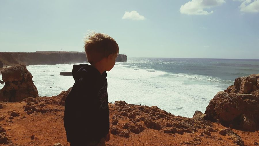 Side view of boy looking at sea against sky