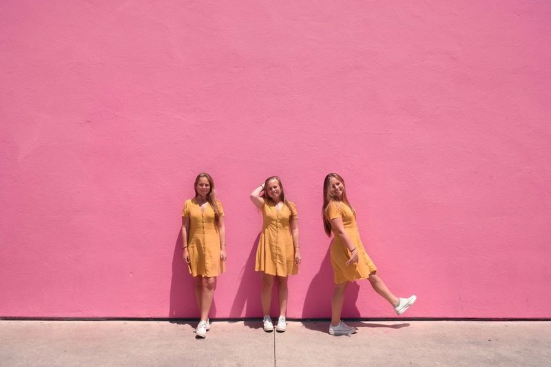 High angle view of women standing against pink wall