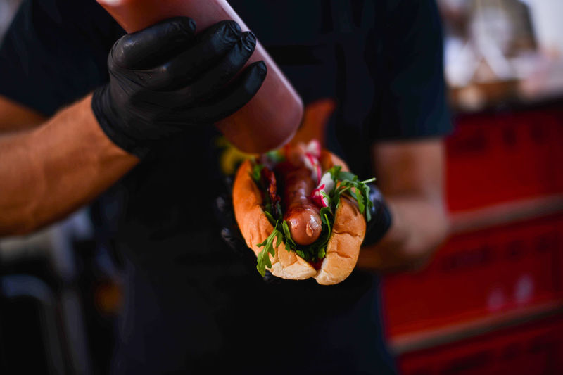 Midsection Of Man Pouring Sauce On Hot Dog At Street