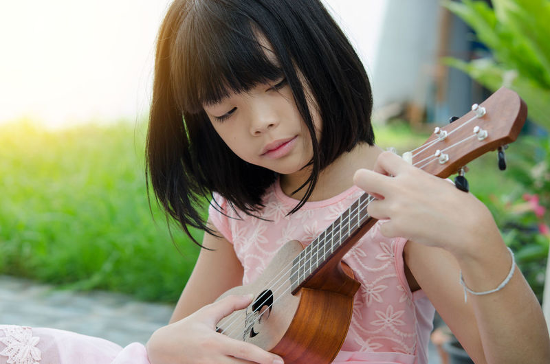 Close-up of girl playing ukulele in park