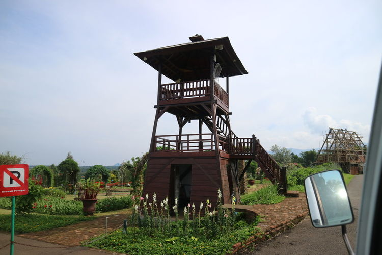 Low angle view of lifeguard tower by building against sky