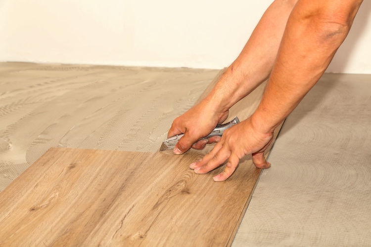 Cropped hand of carpenter installing laminate on floor