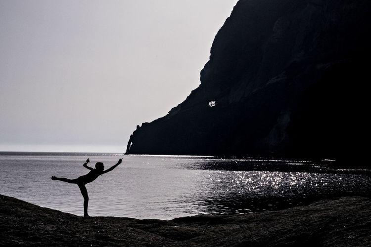 Silhouette girl at beach against clear sky