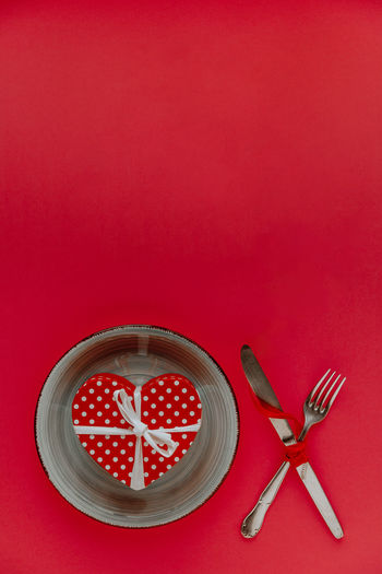 High angle view of heart shape on red table