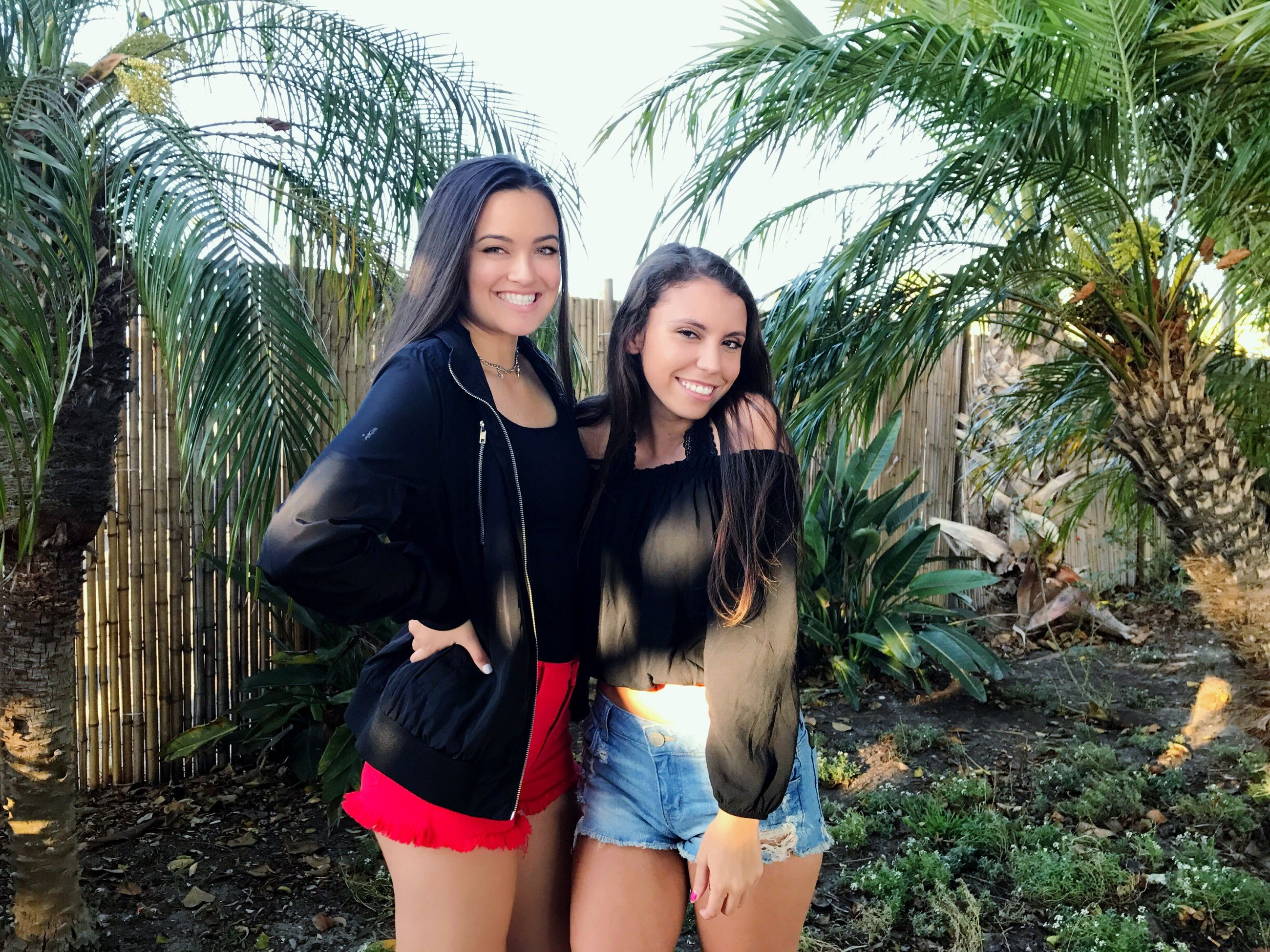 real people, young women, young adult, leisure activity, front view, smiling, three quarter length, happiness, casual clothing, looking at camera, lifestyles, outdoors, two people, tree, standing, day, black hair, togetherness, long hair, beautiful woman, nature, portrait, friendship, growth, palm tree, full length