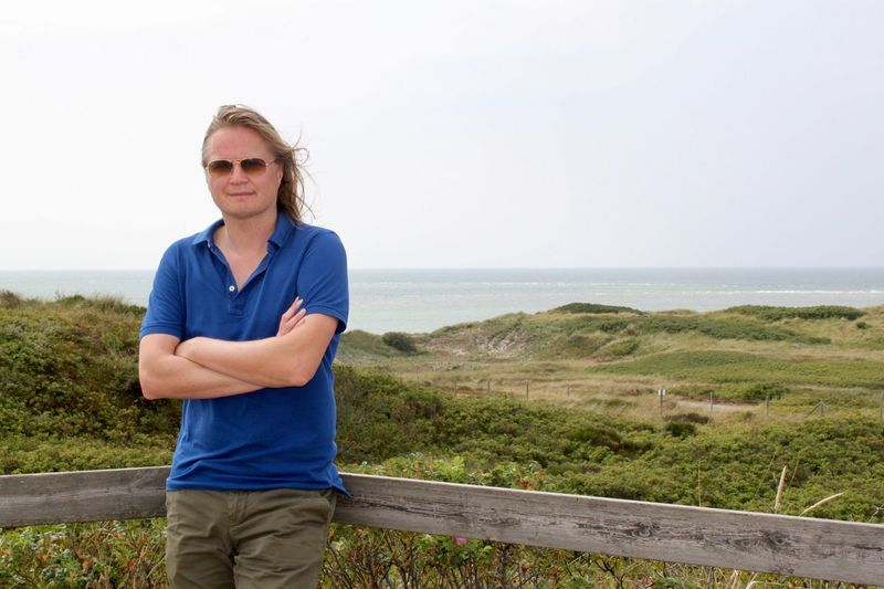 Portrait Of Man With Arms Crossed Wearing Sunglasses Standing Against Sea And Sky