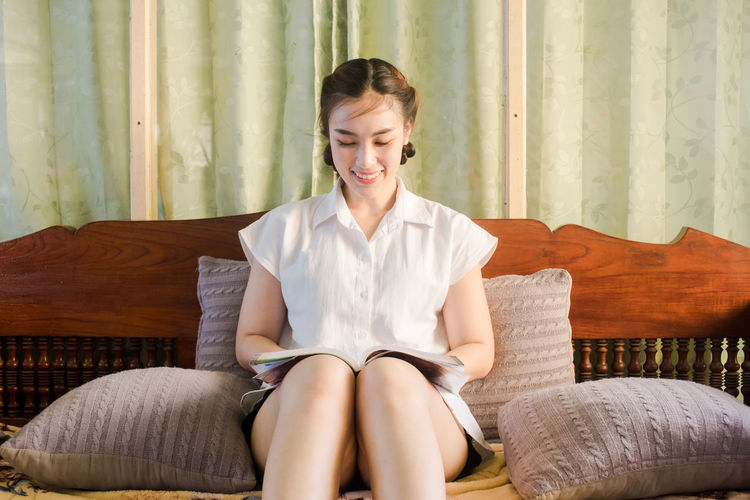 Smiling Young Woman Reading Book While Sitting On Bed At Home