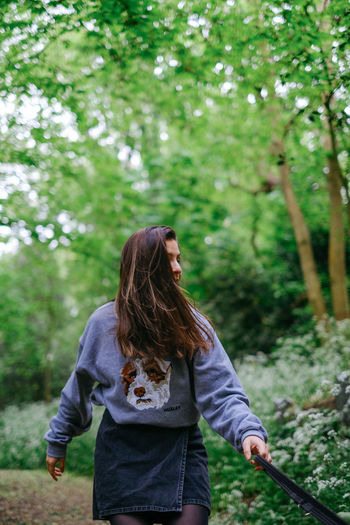 Young woman standing against trees