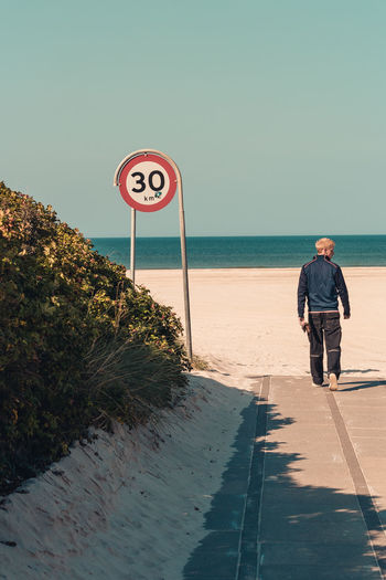 Don't walk too fast. 30 Adult Adults Only Beach Clear Sky Day Dog Rose Full Length Long Goodbye Men Nusshain 04 17 One Man Only One Person Only Men Outdoors People Road Sign Sea Sky Streetphotography Way To Beach Wheelchair Access Wild Rose