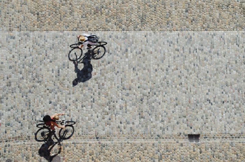 High Angle View Of People Cycling On Street