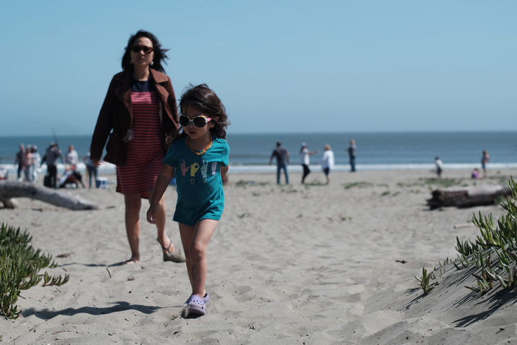 Mother And Daughter Walking At Beach Against Clear Sky On Sunny Day