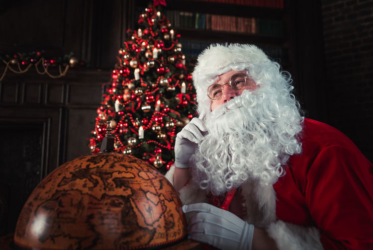 Man wearing santa claus costume by globe at home