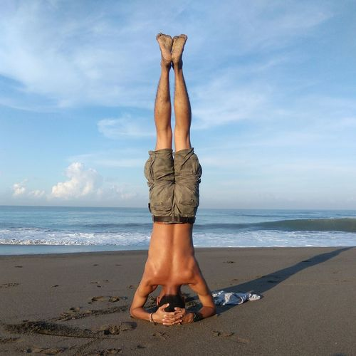 Rear view of shirtless young man doing headstand at beach against sky
