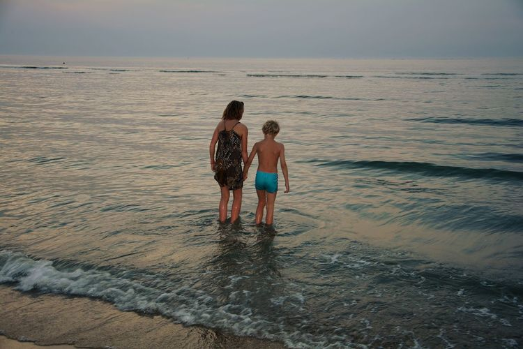 Mother and son wading in sea during sunset
