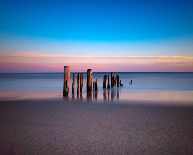 Wooden posts at beach against sky during sunset
